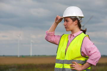 Side view of cute young woman engineer in white helmet and green vest standing on the background of windmills