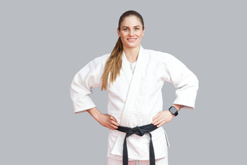 Happy cheerful beautiful blonde young athletic woman in white kimono, black belt standing, holdind hands on waist, toothy smiling and looking at camera. Indoor studio shot, isolated on grey background