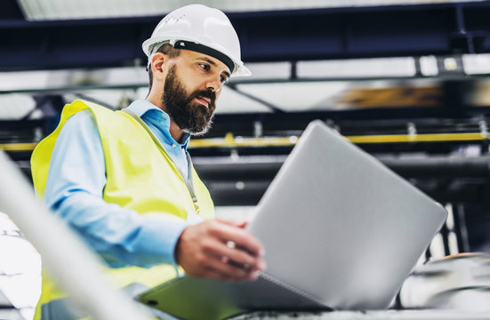 A portrait of an industrial man engineer with laptop in a factory, working.