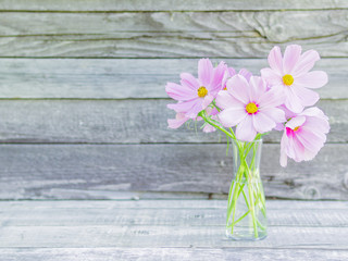 glass vase with a bouquet of pink delicate fragile flowers on wooden background of rough boards, copy space for text