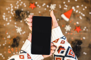 Female hands in a warm knitted sweater holding smart mobile phone with oled display on wooden background with Christmas snowflakes and snow. Happy New Year and Xmas Flat lay composition top view.