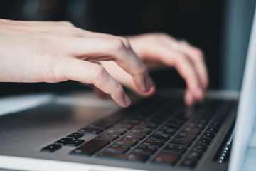 Closeup of woman's hands working on laptop at office. Business woman concept. Horizontal