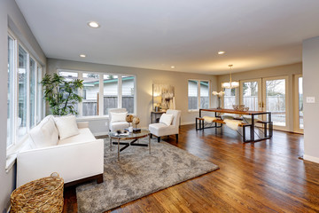 Living room in neutral colors with hardwood floor.