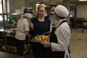 Female manager and female chefs interacting with each other