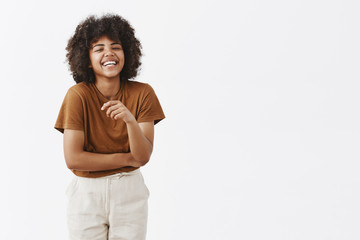 Studio shot of cute african american woman with afro hairstyle in trendy summer outfit having fun laughing out loud from joy and funny joke gesturing with palm chuckling and smiling carefree at camera