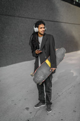 Modern urban young dreadlocks hipster man holding his skate on street and listening music. Standing against black wall with headphones on his head.