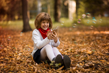 Children and technology concept - girl with smartphone having video call at autumn park