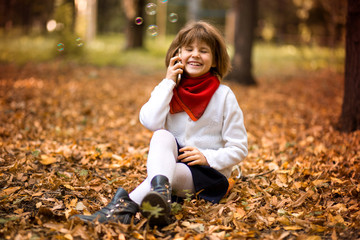 Stylish beautiful little girl holding mobile phone and gladness talk. Technology concept
