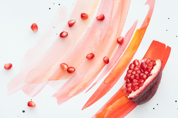 top view of pomegranate piece with seeds on white surface with red watercolor strokes