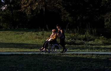 People, one in a wheelchair, take a stroll in a park in Rome