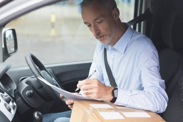 Delivery man writing on paper in delivery van