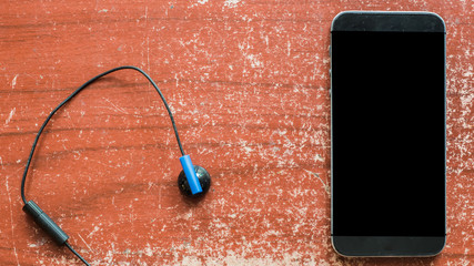 Poster - earphones and smartphone on wooden table.
