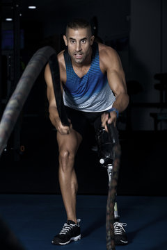 Serious athletic man with battling ropes