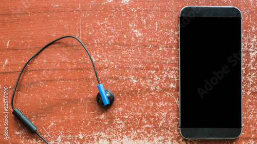 Wall mural earphones and smartphone on wooden table.