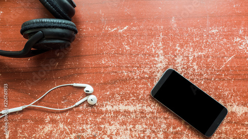 Wall mural smartphone and earphone on wood table