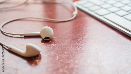 Wall mural white earphone and keyboard  on wood table