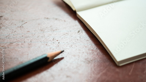 Wall mural pencil close up with notebook on wood table
