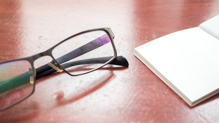 Canvas Print - glasses and notebook on wood table