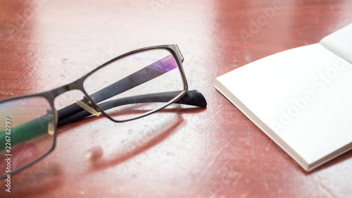 Wall mural glasses and notebook on wood table