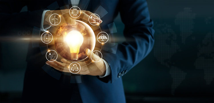 Businessman' s hand holding glowing light bulb with energy sources icon. Campaigning for ecological friendly and sustainable environment.  Elements of this image furnished by NASA