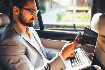 Businessman using smartphone and laptop in a taxi