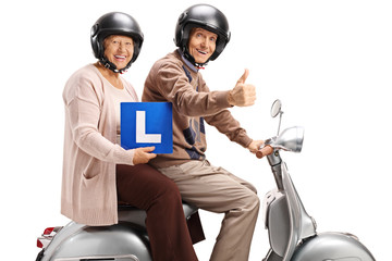 Senior man and woman on a scooter with learner's plate