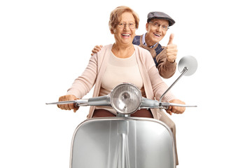Seniors riding a retro scooter making a thumb up gesture