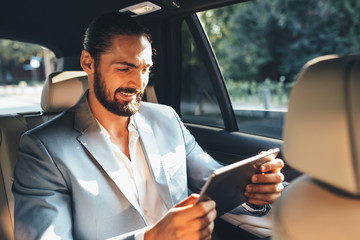 Businessman using digital tablet in a taxi