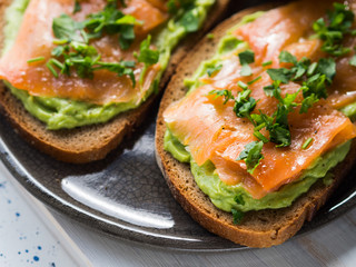 Rye bread avocado toasts with smoked salmon on white wooden board
