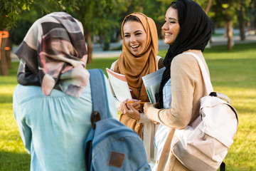 Cheerful young arabian women students holding books in park outdoors talking with each other.