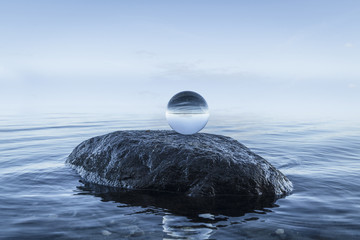 Crystal orb on a black rock by the blue ocean