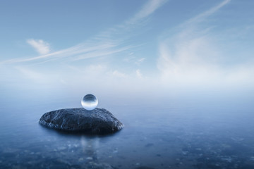 Crystal ball on a rock in a misty seascape