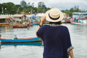 Young women asian wearing a hat, travel back pack View of the fishing harbor Sunset Latinos There is a boat landing. In a fishing village in Rayong, Thailand