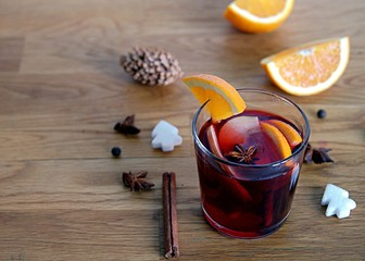 Mulled wine, heated red wine with slices of apple and orange, cinnamon sticks and anise in glass cups on wooden background.