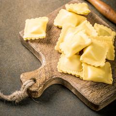 Fresh homemade italian stuffed square pasta ravioli on wooden cutting board. Healthy food concept, gluten free.