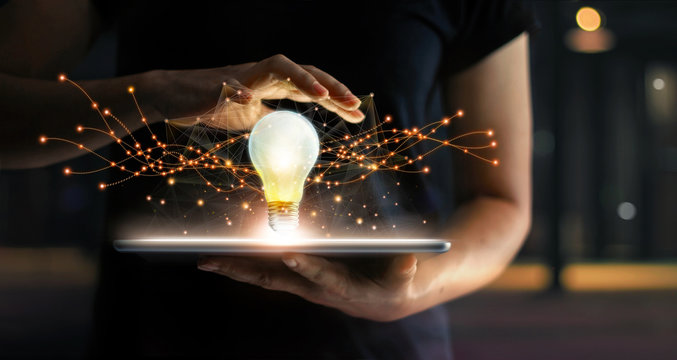 Innovation. Hands holding tablet with light bulb future technologies and network connection on virtual interface background, innovative technology in science and communication concept .