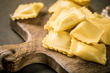 Fresh homemade italian stuffed square pasta ravioli on wooden cutting board. Healthy food concept, gluten free.