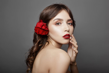 Woman with a big red flower in her hair. Brown-haired girl with a red flower posing on a gray background. Big beautiful eyes and natural makeup. Long curly hair, perfect face