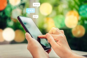 Fototapeta Women hand using smartphone typing, chatting conversation in chat box icons pop up. Social media maketing concept. obraz