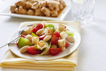 Salad with three kinds of tomatoes, boiled white kidney beans and croutons from white bread