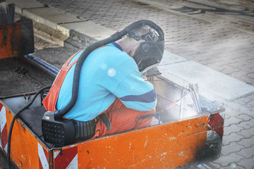 Welders in special suits and oxygen masks perform welding work on the tram tracks.