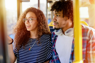Picture of cute young mix race couple sitting in a bus and talking.