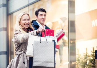 Happy woman and man with Christmas presents in city