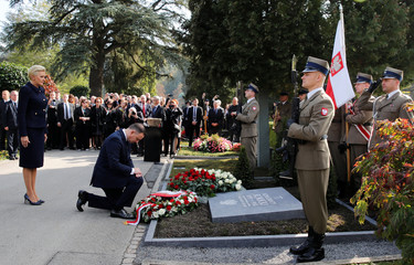 Wife Agata Kornhauser-Duda stands beside as Poland's President Andrzej Duda lays down a wreath on a tombstone commemorating former Polish Consul to Switzerland Konstanty Rokicki in Luzern