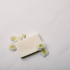 top view of white aromatic soap piece with daisies on white marble surface