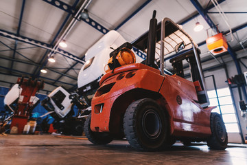 Picture of forklift in car repairing workshop.
