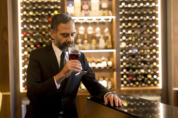Handsome mature man tasting red wine