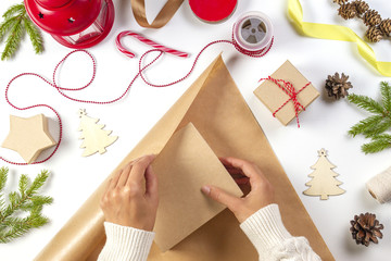 Christmas gift wrapping. Woman's hands packing Christmas present box in craft paper