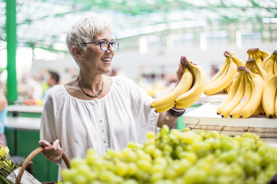 Good-looking senior woman buys bananas at the market