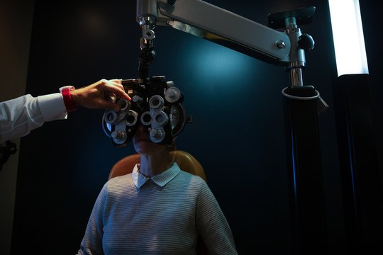 Optometrist examining patient eyes with phoropter
